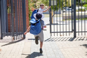 Brother and sister running out of school gates